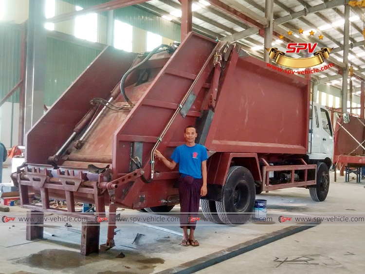 Myanmar workers with half-finished garbage truck